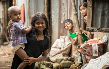 A girl carries a younger boy in a slum in Dhaka, the capital of Bangladesh